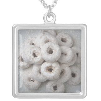 Close-up of powdered doughnuts in a plate silver plated necklace