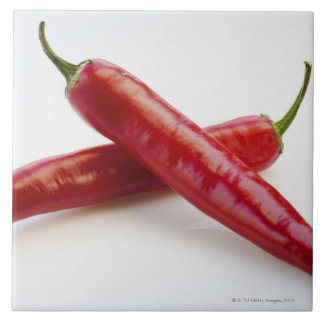 Close up of red chili peppers on white large square tile