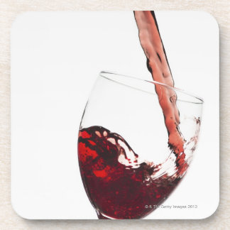 Close up of red wine being poured into glass on coaster