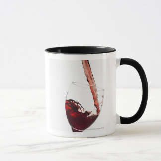 Close up of red wine being poured into glass on mug