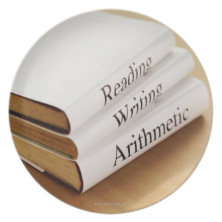 close-up of three books on a wooden surface dinner plate