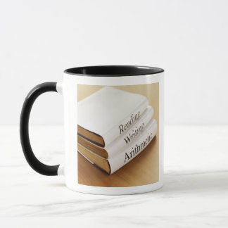 close-up of three books on a wooden surface mug