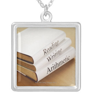 close-up of three books on a wooden surface silver plated necklace