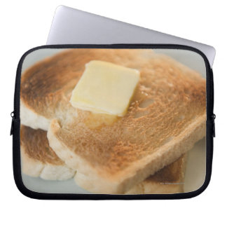 Close up of toasts with butter on plate laptop sleeve