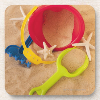 Close up of toys on sand drink coaster