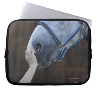 close-up of young girl touching white horse laptop sleeve