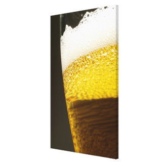 Close up view of beer, bubbles and foam in a canvas print