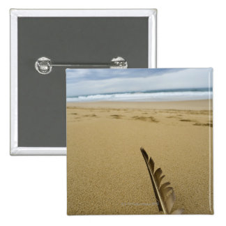 Close-up view of bird feather in beach sand, 15 cm square badge