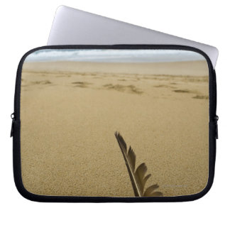Close-up view of bird feather in beach sand, laptop sleeve