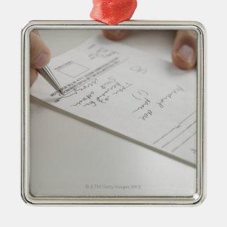 Closeup of hands signing prescription christmas ornament