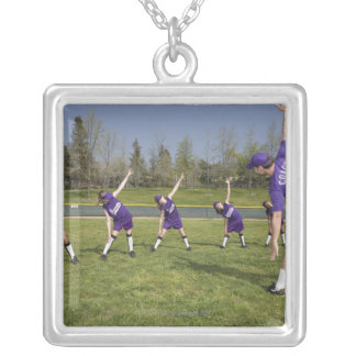 Coach and little league players stretching silver plated necklace