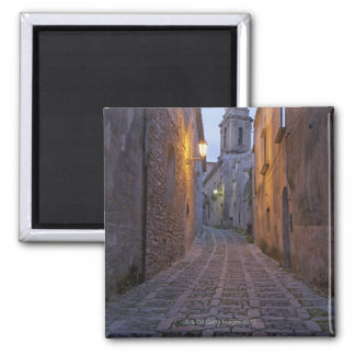 Cobbled alleyway of old city lit up at night square magnet