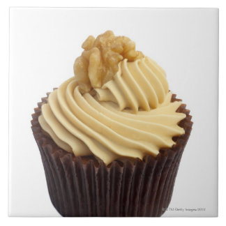 Coffee cupcake topped with coffee cream and a tile