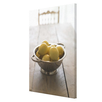 Colander with lemons on wooden table canvas print