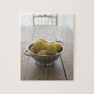 Colander with lemons on wooden table jigsaw puzzle