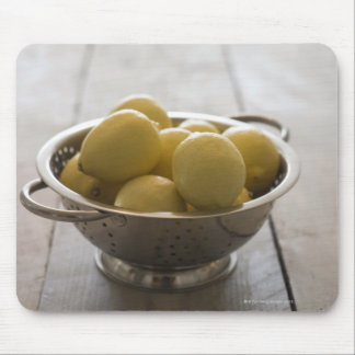 Colander with lemons on wooden table mouse mat