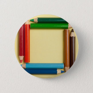 Color pencils forming a square frame 6 cm round badge
