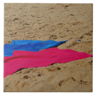 Colored towels on sandy beach tile