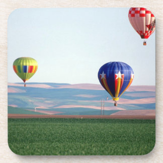 Colorful hot air balloons float over wheat drink coasters