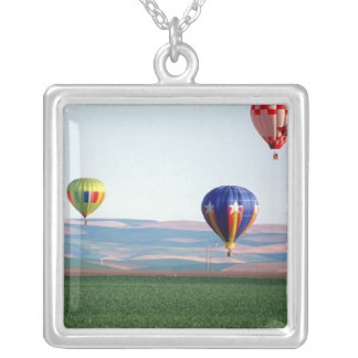 Colorful hot air balloons float over wheat square pendant necklace
