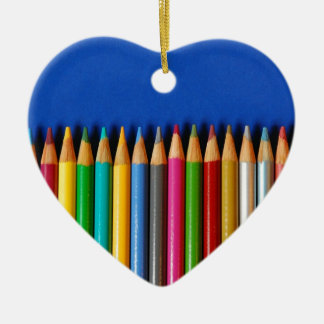 Colorful pencil crayons on blue background ceramic heart decoration