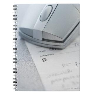 Computer mouse on written prescription notebook