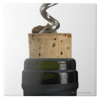 Corkscrew and cork, photographed on white tile