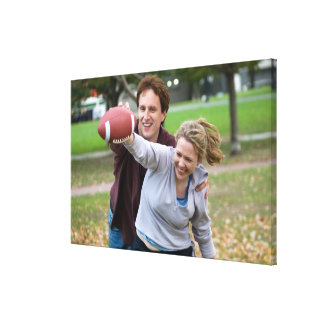 Couple playing football in park canvas print