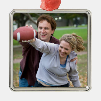 Couple playing football in park christmas ornament