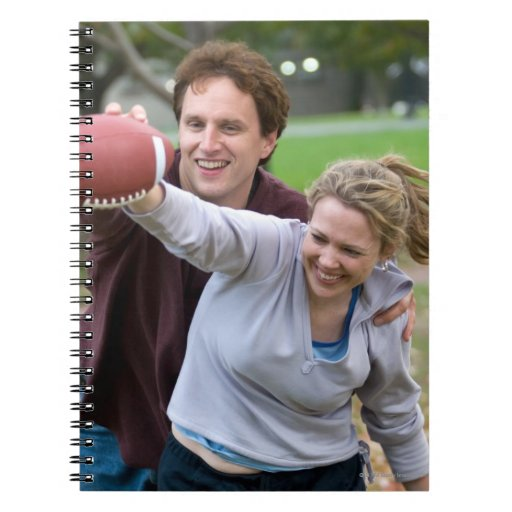 Couple playing football in park note book
