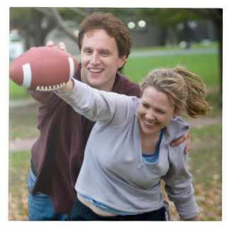Couple playing football in park tile