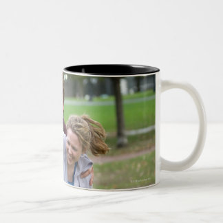 Couple playing football in park Two-Tone coffee mug
