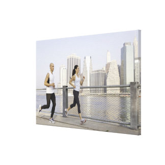 Couple running on pier with city in background canvas prints