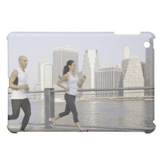 Couple running on pier with city in background cover for the iPad mini