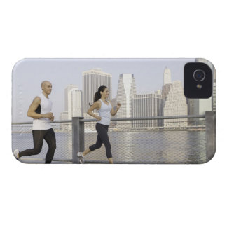 Couple running on pier with city in background iPhone 4 Case-Mate cases