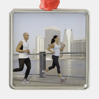 Couple running on pier with city in background Silver-Colored square decoration