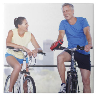 Couple sitting on bicycles tile