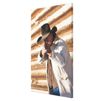 Cowboy aiming his gun, standing by an old log gallery wrapped canvas