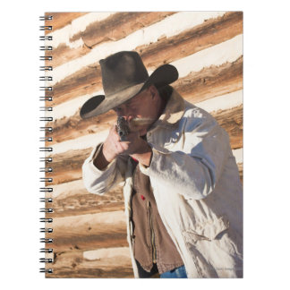 Cowboy aiming his gun, standing by an old log notebook