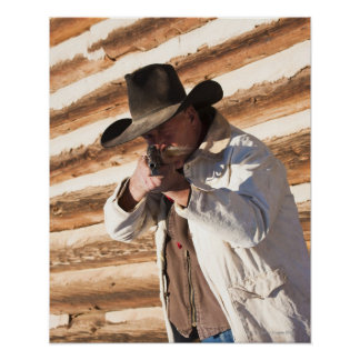 Cowboy aiming his gun, standing by an old log poster
