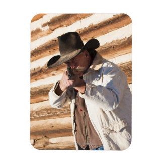 Cowboy aiming his gun, standing by an old log rectangle magnets
