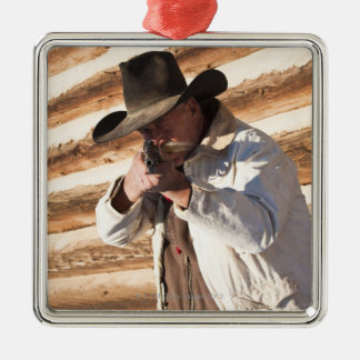 Cowboy aiming his gun, standing by an old log Silver-Colored square decoration