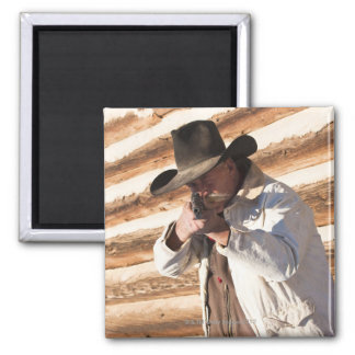 Cowboy aiming his gun, standing by an old log square magnet