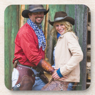 Cowboy and cowgirl holding hands in front of an coaster