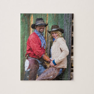 Cowboy and cowgirl holding hands in front of an jigsaw puzzle