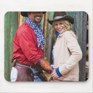 Cowboy and cowgirl holding hands in front of an mouse pad