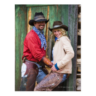 Cowboy and cowgirl holding hands in front of an postcard