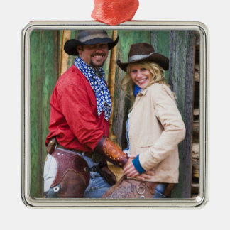 Cowboy and cowgirl holding hands in front of an Silver-Colored square decoration