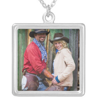 Cowboy and cowgirl holding hands in front of an silver plated necklace