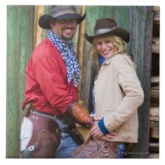 Cowboy and cowgirl holding hands in front of an tile